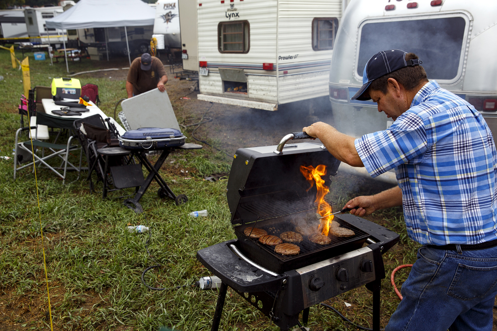"Making the best of a bad situation, Greg Keyser grills hamburgers during a break from cleaning up his trailer in Happy Hollow at the Illinois State Fairgrounds Saturday Aug. 13, 2016. ""They were in the freezer and beginning to thaw,"" he said. His Airstream camper suffered extensive damage and was filled with up to two feet of water during the height of a torrential downpour that flooded the area Friday evening. Rich Saal/The State Journal-Register"