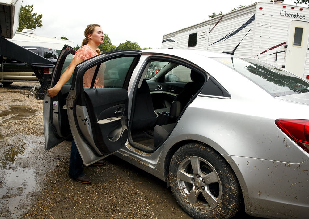 Mallory Rutz inspects the damage to her 2015 Chevy Cruze, which filled with water above the door handles when the Happy Hollow area at the Illinois State Fairgrounds flooded Friday evening during a torrential rain. Rutz said Saturday, Aug. 13, 2016 that she thought the car would be a total loss. Rich Saal/The State Journal-Register