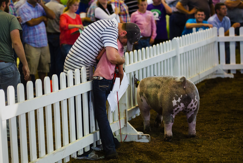 Andy Rash wraps his daughter Averey in a bear hug after she won Reserve Grand Champion Wether during the Parade of Champions in the Coliseum at the Illinois State Fair Saturday, Aug. 13, 2016. Ted Schurter/The State Journal-Register