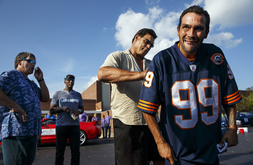 "Members of the 1985 Chicago Bears Steve McMichael, left, and Otis Wilson wait as teammate Dan Hampton, also known as ""Danimal,"" signs his autograph on the back of David Willer's Hampton jersey before the Illinois State Fair Twilight Parade Thursday, Aug. 11, 2016. The three Bears served as Grand Marshals for the parade. Ted Schurter/The State Journal-Register"