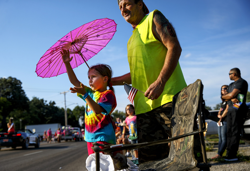 Brooklynn Dibler watches the Illinois State Fair Twilight Parade under an umbrella held by her grandfather Dave Thorpe Thursday, Aug. 11, 2016. Ted Schurter/The State Journal-Register
