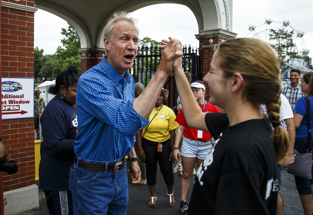 Illinois Gov. Bruce Rauner gets a high five from Abbey Twitchell, of Greenfield, Ill., as he congratulated her on singing the National Anthem for the ribbon cutting to open the 2016 Illinois State Fair at the Main Gate of the fairgrounds, Friday, Aug. 12, 2016, in Springfield, Ill. Justin L. Fowler/The State Journal-Register