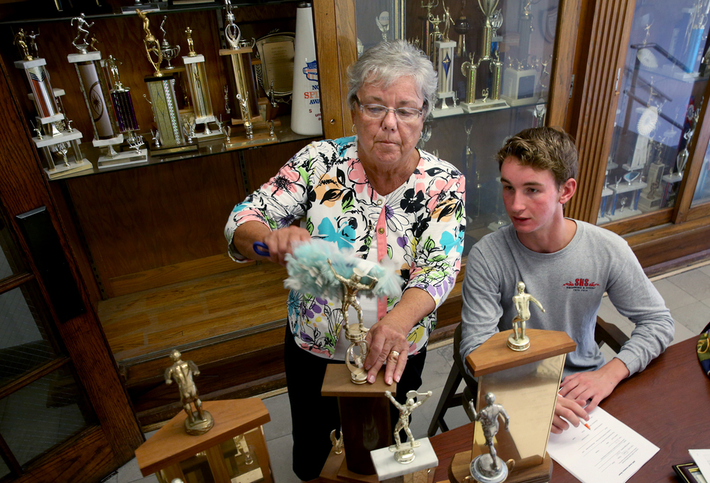 Barb Zuspann of Springfield, who donated money in 1985 to Springfield High School in the memory of her husband that was used to build some of the trophy display cases, cleans some of the trophies while Jake Frech catalogues them at the school on Friday, July 29, 2016. Springfield High School rising senior Jake Frech is working on his eagle scout project that involves cataloguing the hundreds of trophies won by his school as part of the school's centennial this fall. David Spencer/The State Journal-Register