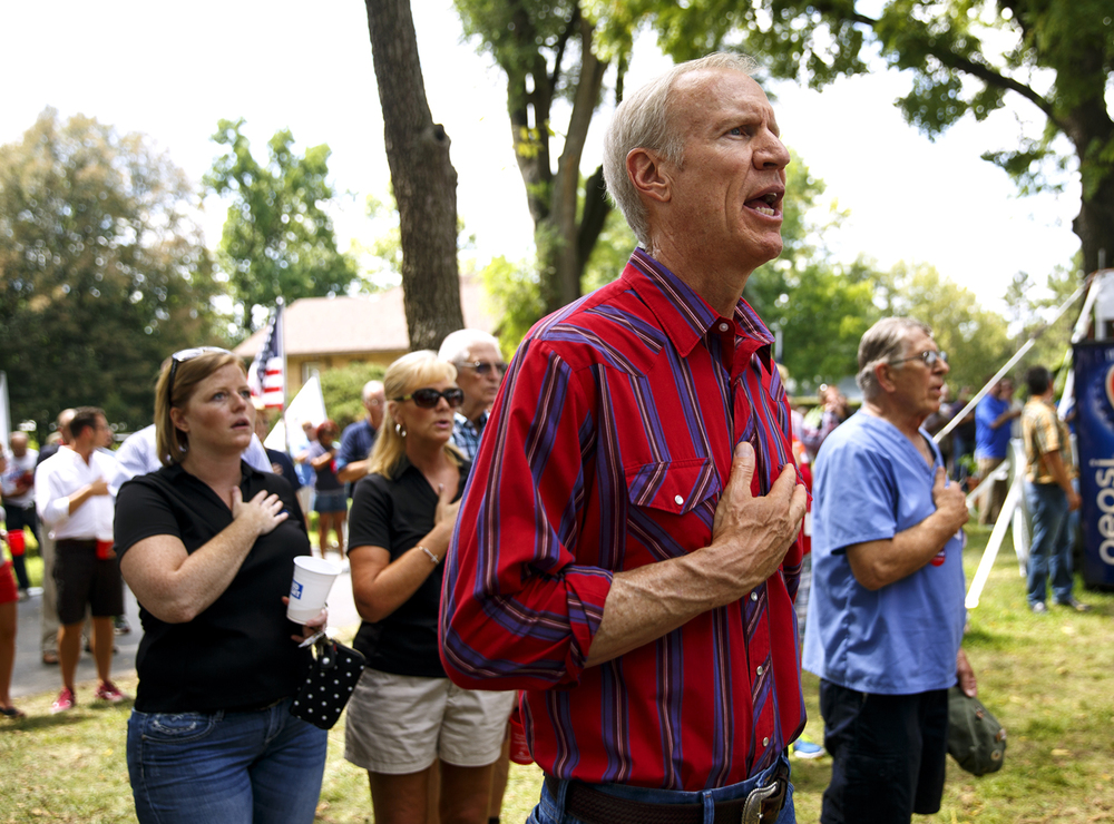 Gov. Bruce Rauner sings along to the National Anthem at the start of the Republican Day rally on the Director's Lawn at the Illinois State Fair Wednesday, Aug. 17, 2016. Rich Saal/The State Journal-Register