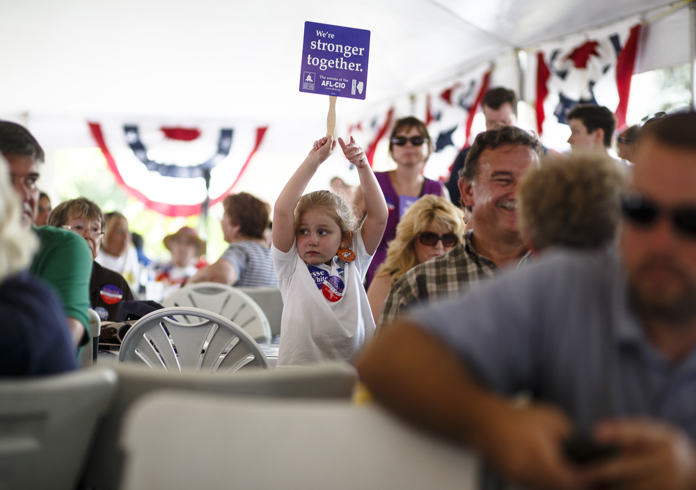 Sophia DelGiorno, 5, the daughter of State Representative democratic candidate Tony DelGiorno, waves a political sign in the air as the Democrats take the stage during Democrat Day on the Directors Lawn at the Illinois State Fairgrounds, Thursday, Aug. 18, 2016, in Springfield , Ill. Justin L. Fowler/The State Journal-Register