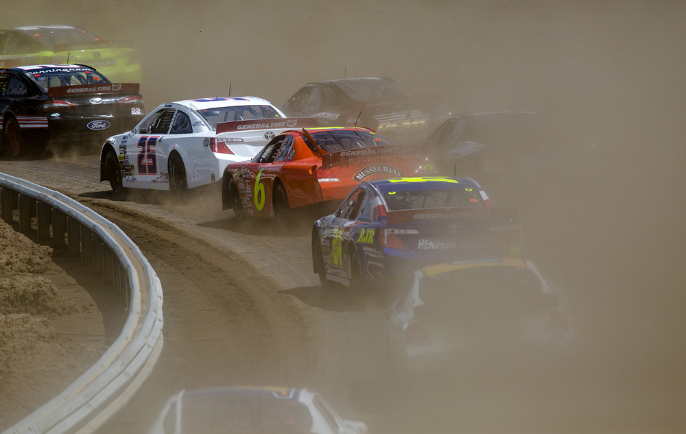 Josh Williams orange Chevrolet stands out in the cloud of dust as racers plow through the first turn during the 54th annual SuperChevyStores.com-Allen Crowe 100 at the Illinois State Fair Sunday, Aug. 21, 2016. Ted Schurter/The State Journal-Register