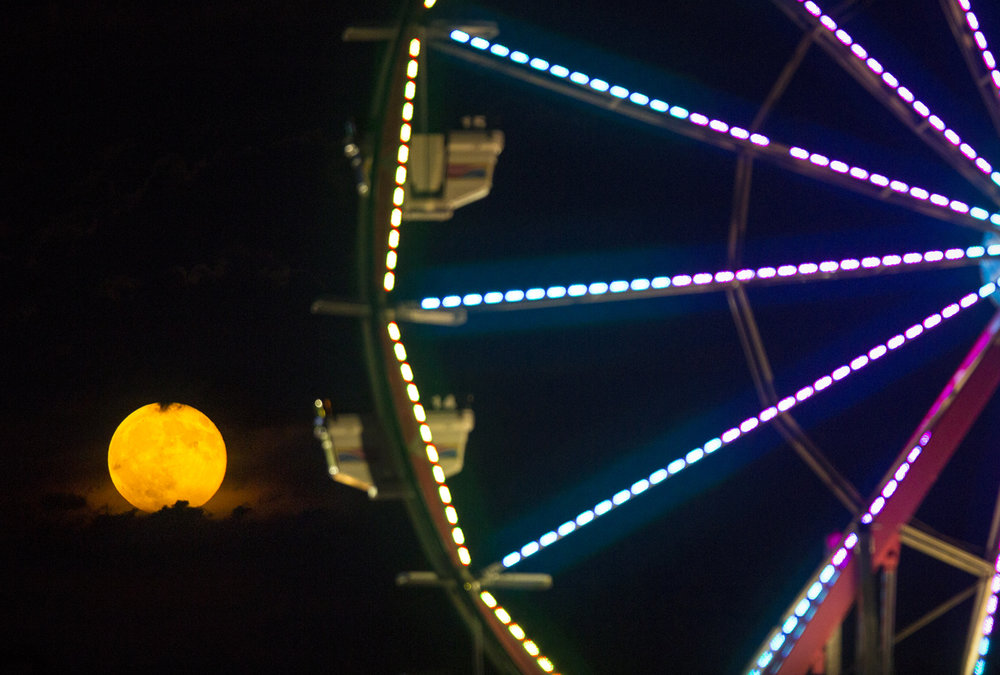 A waning gibbous moon rises in the sky behind a ferris wheel at the Illinois State Fair Thursday, Aug. 18, 2016. Ted Schurter/The State Journal-Register