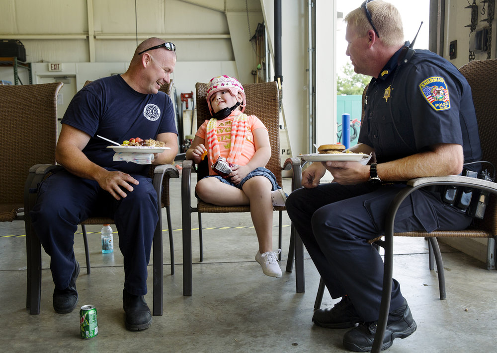 Sherman firefighter Beau Friday, left, and Sherman Police Sgt. Aaron Entringer laugh with Abigail Peddycoart as they visit during a combination birthday homecoming party for the seven-year-old who suffered multiple skull fractures, facial fractures and two different types of brain bleeding in a single-vehicle crash June 20 just north of Sherman on Illinois 124. Friday and Entringer were the first rescue workers on the scene and their quick assessment of Peddycoart's head trauma facilitated her prompt transport to the hospital and contributed to her survival. Ted Schurter/The State Journal-Register