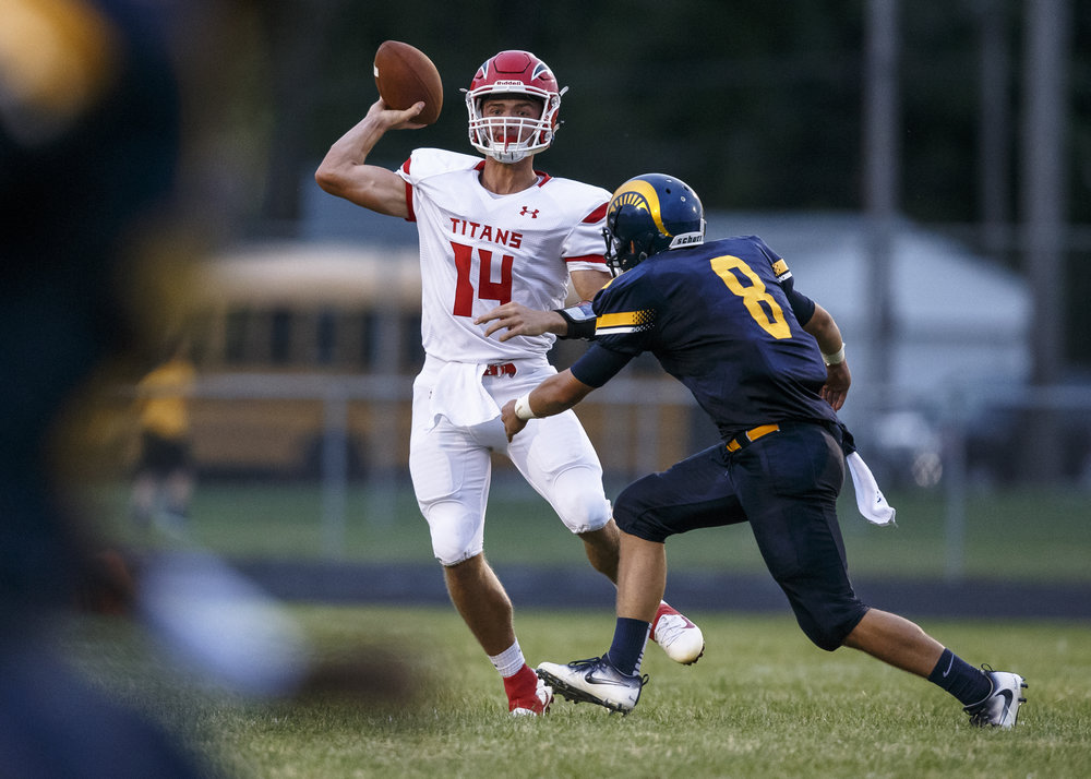 Glenwood quarterback Cole Hembrough (14) is forced out of the pocket on a throw by Southeast's Cody Louveau (8) during the first half at Southeast High School, Friday, Aug. 26, 2016, in Springfield, Ill. Justin L. Fowler/The State Journal-Register