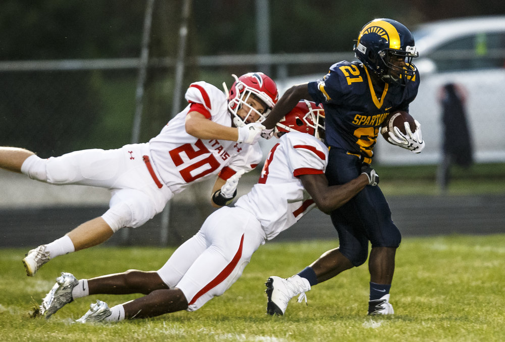 Southeast's Vincent Hill (21) is brought down by Glenwood's Austin Schiff (20) and Brandon Hay (8) after  catch during the first half at Southeast High School, Friday, Aug. 26, 2016, in Springfield, Ill. Justin L. Fowler/The State Journal-Register