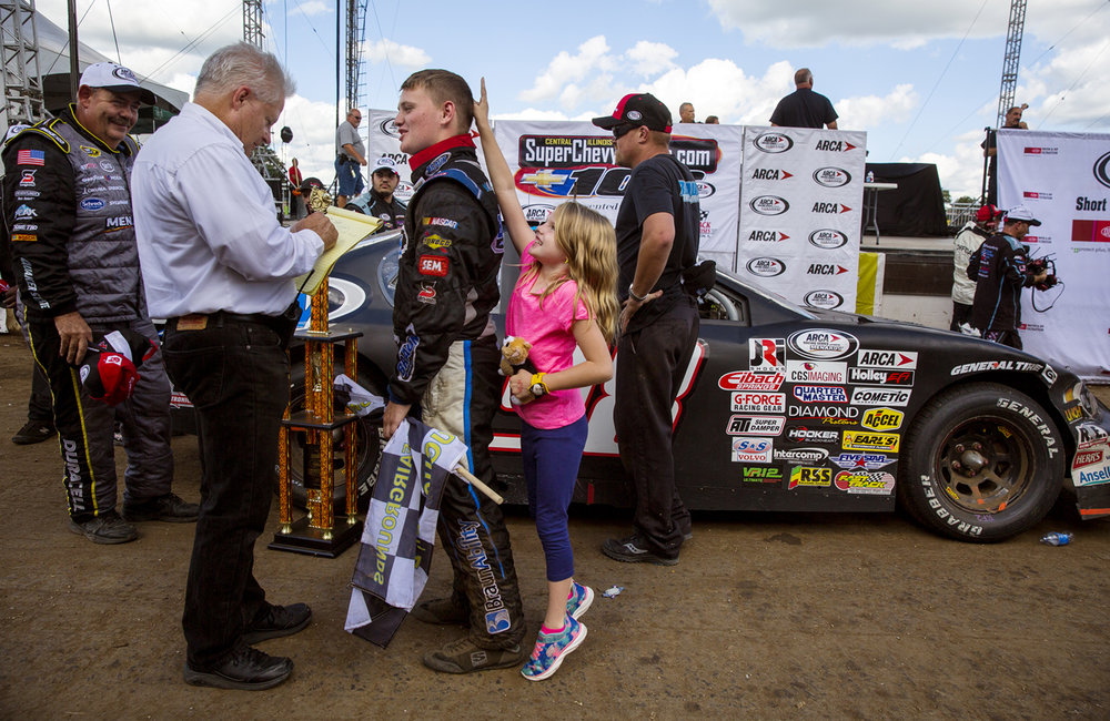 Justin Haley's little sister Lindy Dennis makes bunny ears behind him as he answers questions after winning the 54th annual SuperChevyStores.com-Allen Crowe 100 and becoming the all-time youngest winner at the Illinois State Fairgrounds in championship auto racing history Sunday, Aug. 21, 2016. Ted Schurter/The State Journal-Register
