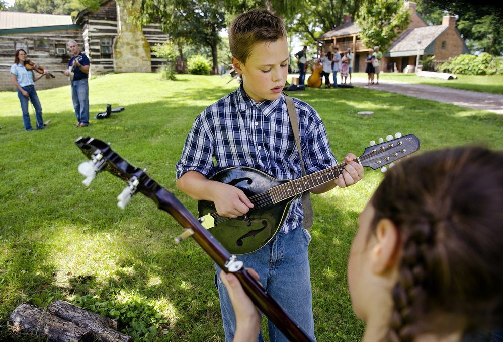 Robert Templeton warms up on mandolin as his sister Margaret plays banjo on the grounds of the Clayville Historic Site during the Clayville Folk Music Festival Saturday, Aug. 27, 2016. The siblings were later joined by five more who performed on the acoustic Music in the Woods stage during the annual show. Ted Schurter/The State Journal-Register