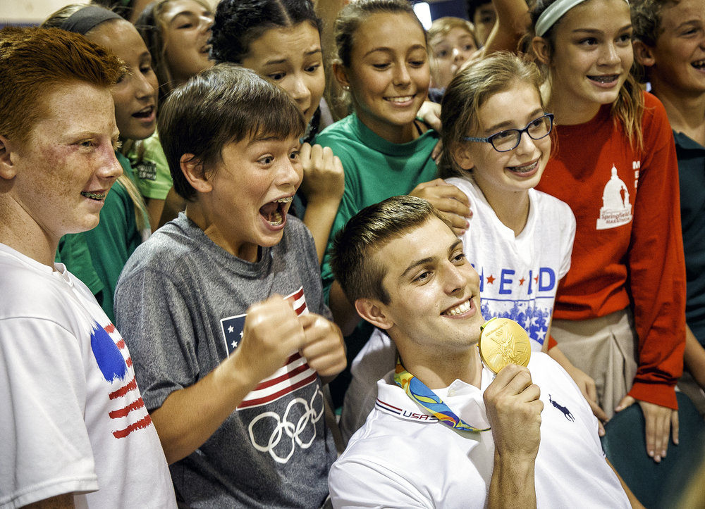 Christ the King eighth grader Connor Moore, left, reacts after getting to touch the Olympic gold medal of Sacred Heart-Griffin High School graduate Ryan Held, during an assembly to celebrate Held's achievements at Christ the King School, which he is a 2010 graduate, Friday, Sept. 2, 2016, in Springfield, Ill. Justin L. Fowler/The State Journal-Register