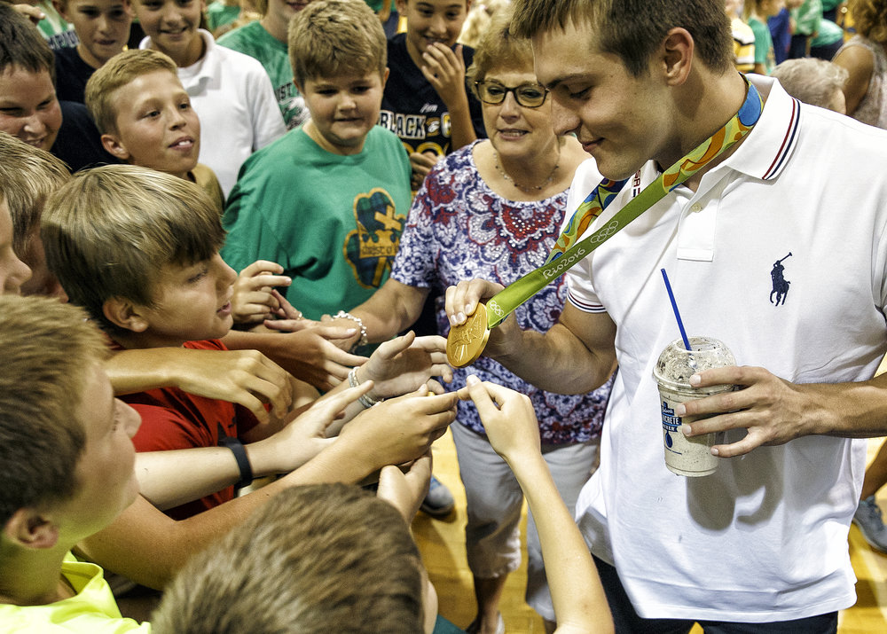 Sacred Heart-Griffin High School graduate Ryan Held is rushed by students of his former school, Christ the King School, which he is a 2010 graduate, for a chance to touch his Olympic gold medal during an assembly to celebrate his achievements, Friday, Sept. 2, 2016, in Springfield, Ill. Justin L. Fowler/The State Journal-Register