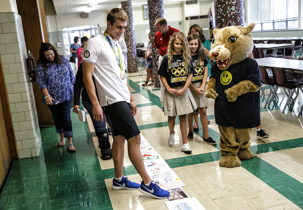 Sacred Heart-Griffin High School graduate Ryan Held, center, points out a picture of a cat, in the path of hand made posters leading him to the gymnasium for an assembly to celebrate his Olympic gold medal at his former school, Christ the King School, Friday, Sept. 2, 2016, in Springfield, Ill. Held's Twitter bio states that he is an avid watcher of cat videos. Justin L. Fowler/The State Journal-Register