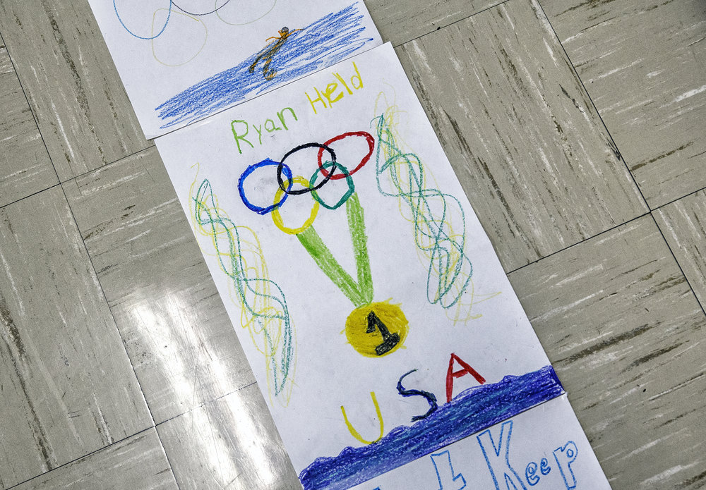 The students at Christ the King School made a path with handmade posters to help lead Sacred Heart-Griffin High School graduate Ryan Held, and a 2010 graduate of Christ the King, to the gymnasium for an assembly to celebrate his Olympic gold medal, Friday, Sept. 2, 2016, in Springfield, Ill. Justin L. Fowler/The State Journal-Register