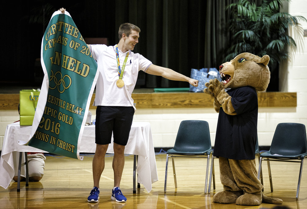 Sacred Heart-Griffin High School graduate Ryan Held, left,  gets a fist bump from the Christ the King School Cougar Cub, seventh grader Sophia Gebhardt, after the unveiling of his banner to be hung in the gym for his Olympic gold medal during an assembly to celebrate his achievements at his former school, Friday, Sept. 2, 2016, in Springfield, Ill. Justin L. Fowler/The State Journal-Register