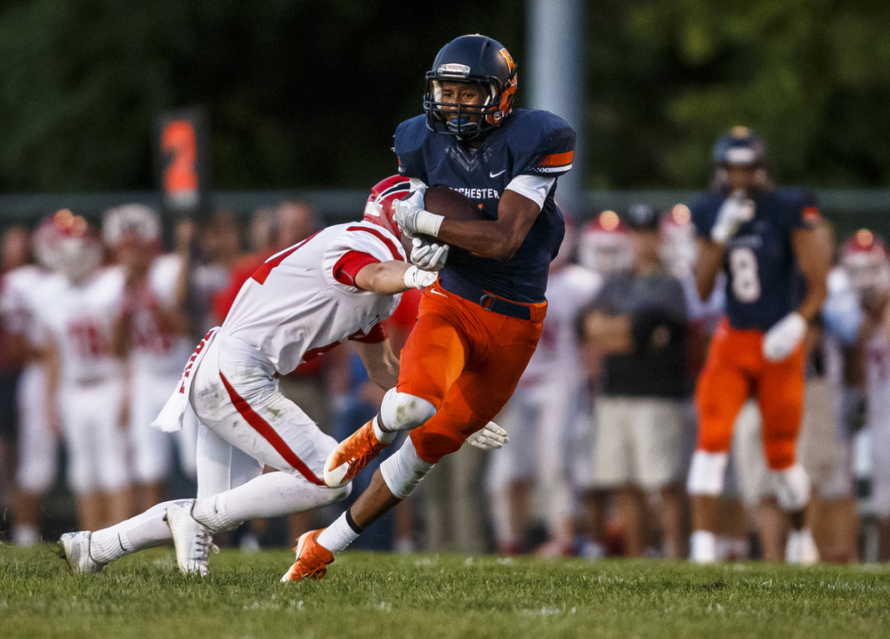 Rochester's D'Ante Cox (1) avoids a tackle from Glenwood's Austin Schiff (20) after catching a pass across the middle during the first half at Rocket Booster Stadium, Friday, Sept. 2, 2016, in Rochester, Ill. Justin L. Fowler/The State Journal-Register