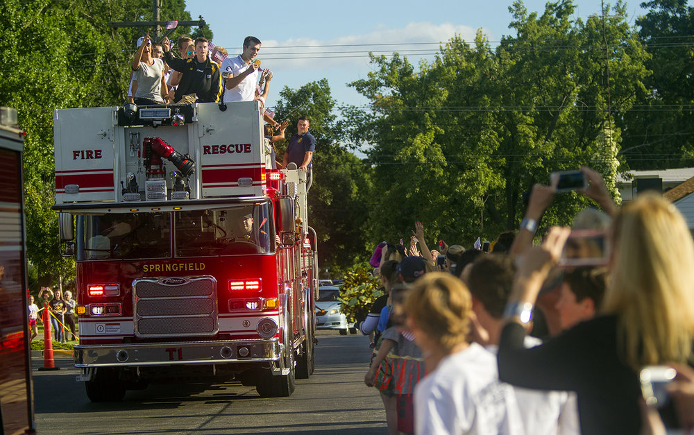 Ryan Held holds out his Olympic medal for the crowd to see as he arrives on Springfield Fire Department Truck One before his alma mater Sacred Heart-Griffin faced Decatur MacArthur at Cyclone Stadium Friday, Sept. 2, 2016. Illinois Gov. Bruce Rauner declared the Friday Ryan Held Day during a ceremony at halftime. Ted Schurter/The State Journal-Register