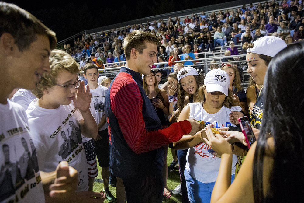 Ryan Held shows his Olympic gold medal to members of the Sacred Heart-Griffin swim teams before being honored at halftime of the SHG football game against Decatur MacArthur at Cyclone Stadium Friday, Sept. 2, 2016. Held, an SHG alum, was a member of the United States' first-place 4x100-meter relay team in the Rio de Janeiro 2016 Summer Olympics. Ted Schurter/The State Journal-Register