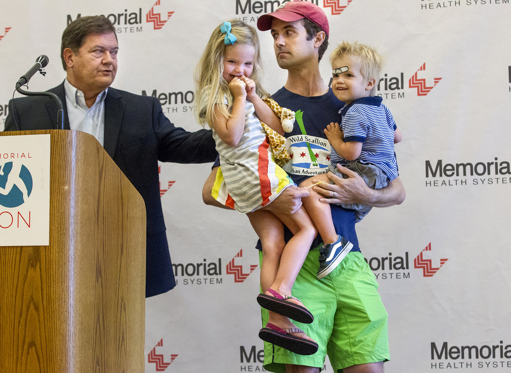 Memorial Health System chief executive officer Ed Curtis pats Zach Adair on the shoulder as he carries his children Piper and Beckett off the podium after speaking about his late father Dr. Daniel Adair before the start of the first Dan Adair, MD, Memorial Triathlon Sunday, Aug. 28, 2016 at the Kerasotes YMCA.  Adair helped launch Memorial's SportsCare program in 1985 and the AthletiCare program at HSHS St. John's Hospital in 1998. More recently, Adair was co-medical director of SportsCare and part of Springfield Clinic Sports Medicine. Ted Schurter/The State Journal-Register