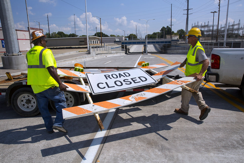 Sam Wright, left, and Cliff Hoenes with Halverson Construction remove the last barricade before opening the Carpenter Street underpass to vehicular traffic after a ribbon cutting ceremony Monday, Aug. 29, 2016. Ted Schurter/The State Journal-Register