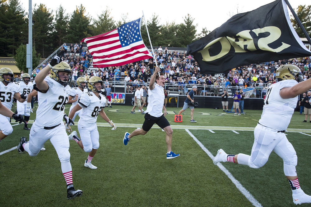 Ryan Held carries the American flag as he takes to the field with the Sacred Heart-Griffin football team at Cyclone Stadium Friday, Sept. 2, 2016. Held, an SHG alum, was a member of the United States' first-place 4x100-meter relay team in the Rio de Janeiro 2016 Summer Olympics. Illinois Gov. Bruce Rauner declared the day Ryan Held Day during a halftime ceremony. Ted Schurter/The State Journal-Register