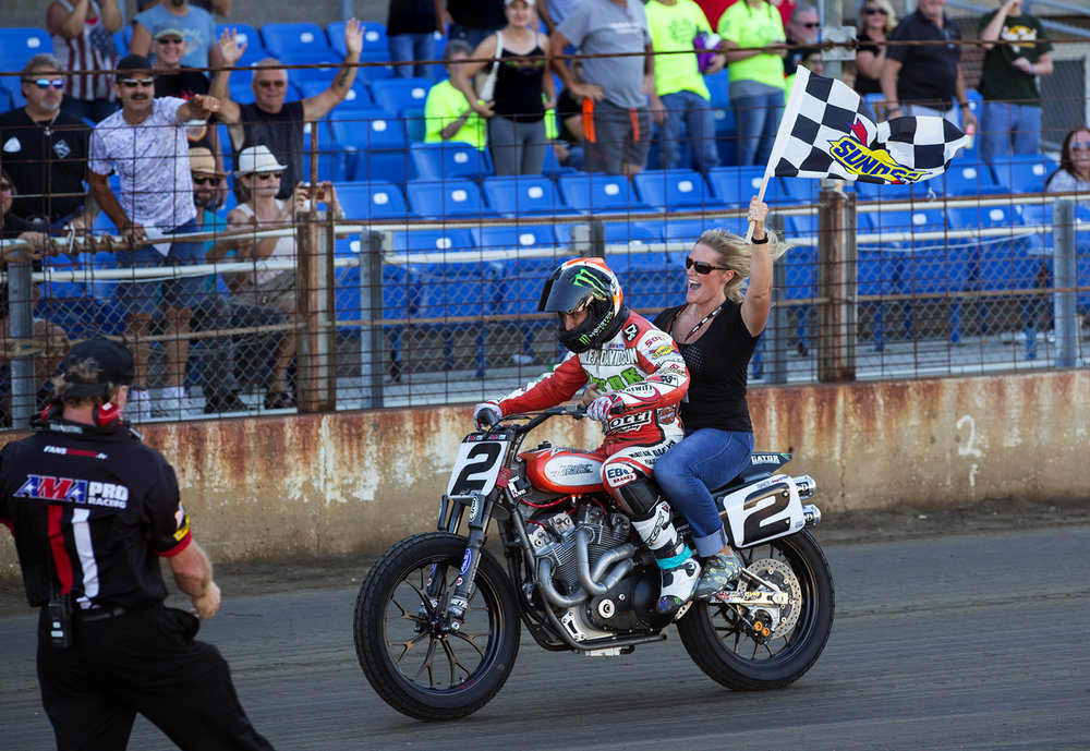 Kenny Coolbeth, Jr.'s wife Jen waves the checkered flag as he takes a victory ride after defeating Bryan Smith by .009 seconds to win the AMA Pro Flat Track Springfield Mile II at the Illinois State Fairgrounds Sunday, Sept. 4, 2016. Ted Schurter/The State Journal-Register