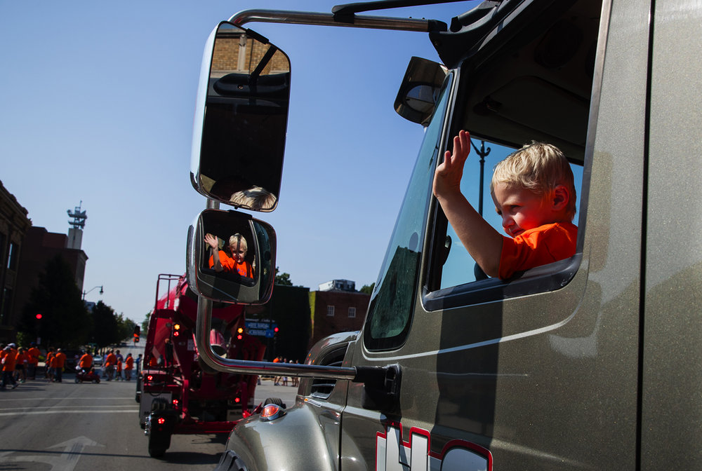 Four-year-old Bentley Johnson waves from the cab of his dad Ben's concrete truck as they participate in the Springfield Labor Day Parade Monday, Sept. 5, 2016.  Ted Schurter/The State Journal-Register