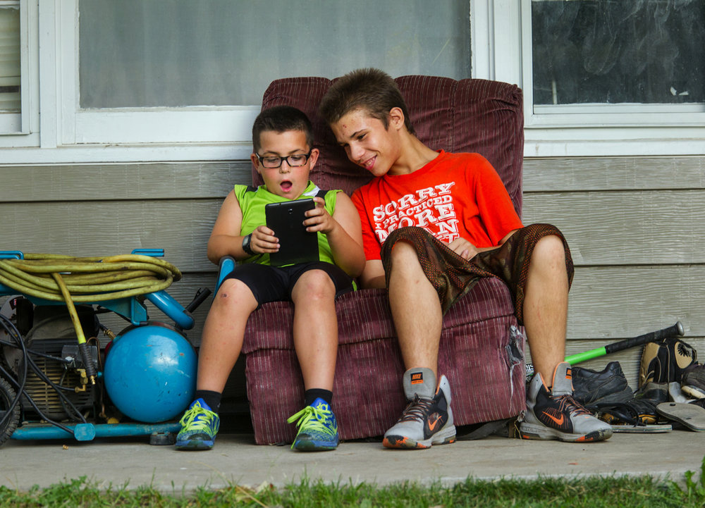 Mason Wann, left, and Isaac Vargas share a chair on Vargas' front porch as Wann plays Clash of Royale, a live multiplayer game, on his tablet Wednesday, Sept. 7, 2016. Ted Schurter/The State Journal-Register