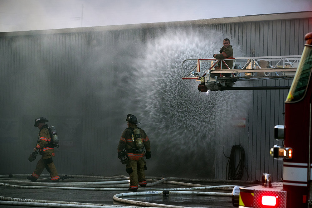 Springfield firefighters spray water into an open door of Hobb-e-Mart, 2875 N. Dirksen Parkway, as they try to get the fire under control Tuesday, Sept. 13, 2016. Ted Schurter/The State Journal-Register