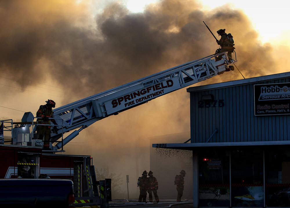 A Springfield firefighter tests the roof of the Hobb-e-Mart building before climbing down to ventilate the roof Tuesday, Sept. 13, 2016. Ted Schurter/The State Journal-Register