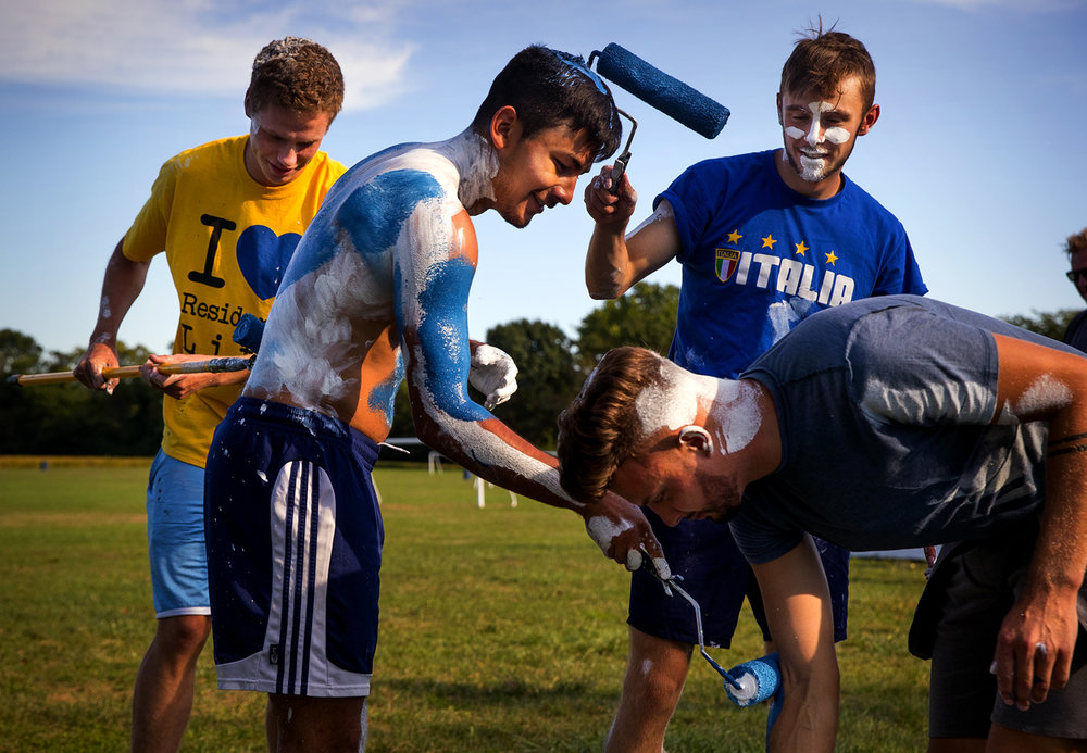 Members of the UIS men's soccer team, from left, Ryley Flynn, Ricky Estrada, Zach Downing and Daniel Kemp paint each other in white and blue paint as they help re-paint the kick boards at the YMCA soccer fields Monday, Sept. 12, 2016. The team received volunteer community service hours for their work.  Ted Schurter/The State Journal-Register