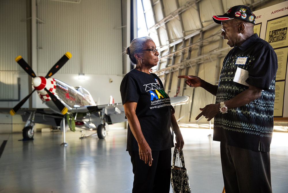 Jerrie Blakely, left, visits with Ocheng Jany during a reception at Abraham Lincoln Capital Airport for the traveling museum exhibit Tuskegee Airmen: Rise Above Tuesday, Sept. 13, 2016. In addition to a P-51 the squadron flew, the exhibit features 160-degree panoramic movie screen inside a 53-foot, temperature-controlled tractor-trailer with expandable sides allowing it to accommodate 30 to 40 people. Ted Schurter/The State Journal-Register