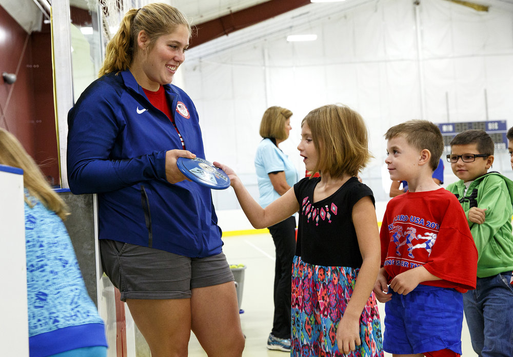 Olympic athlete Kelsey Card visited Carlinville Primary School Monday, Sept. 12, 2016 to speak with kids about her experience in the discus competition this  summer at the Rio Olympics. Second grader Madison Tracy examines the discus Card has used throughout her career. Card grew up in the Macoupin County community and told the kids about how she became interested in the sport when she was in grade school and encouraged them to work hard on their goals. She also told them she'll start soon on training for the 2020 summer games in Japan. Rich Saal/The State Journal-Register
