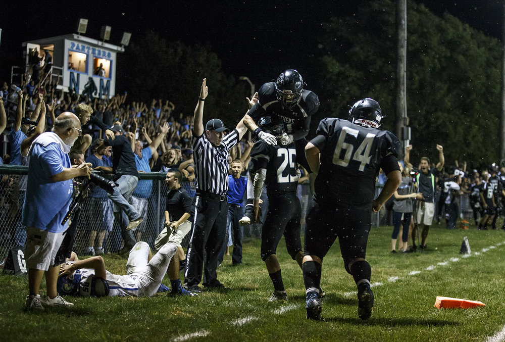 North Mac's Asa Donaldson (21) leaps into the arms of North Mac's Kendall Bearden (25) after he scored on a two point conversion to put the Panthers up 15-14 against North Mac with 24 seconds left in the game at North Mac High School, Friday, Sept. 23, 2016, in Virden, Ill. Justin L. Fowler/The State Journal-Register