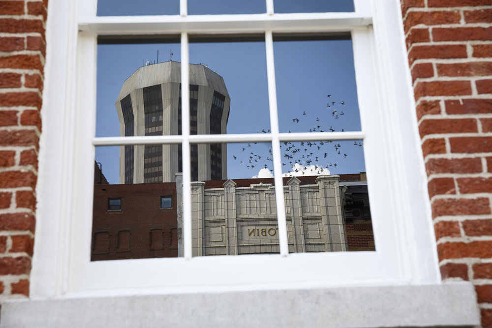 The Tobin building and Wyndham hotel are reflected in a window on the third floor of the Lincoln Herndon law office where hand-lettered signage is being recreated to make the building look like it did in the 1840s. Rich Saal/The State Journal-Register