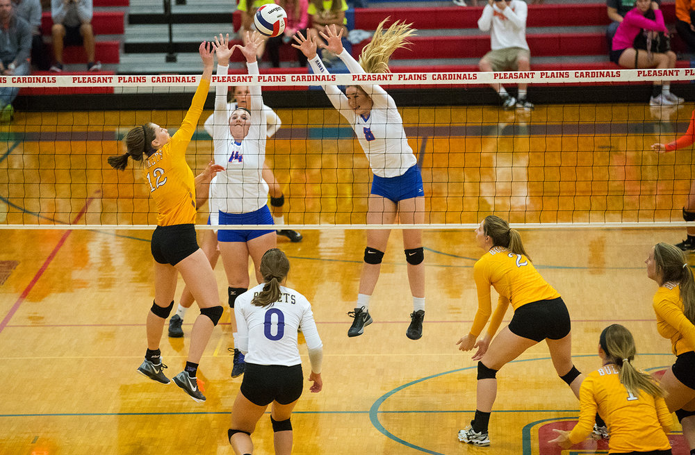 Williamsille's Delaney Edwards tips the ball over a pair of Riverton defenders during the Sangamon County Volleyball Tournament championship game at Pleasant Plains High School Monday, Sept. 26, 2016. Ted Schurter/The State Journal-Register