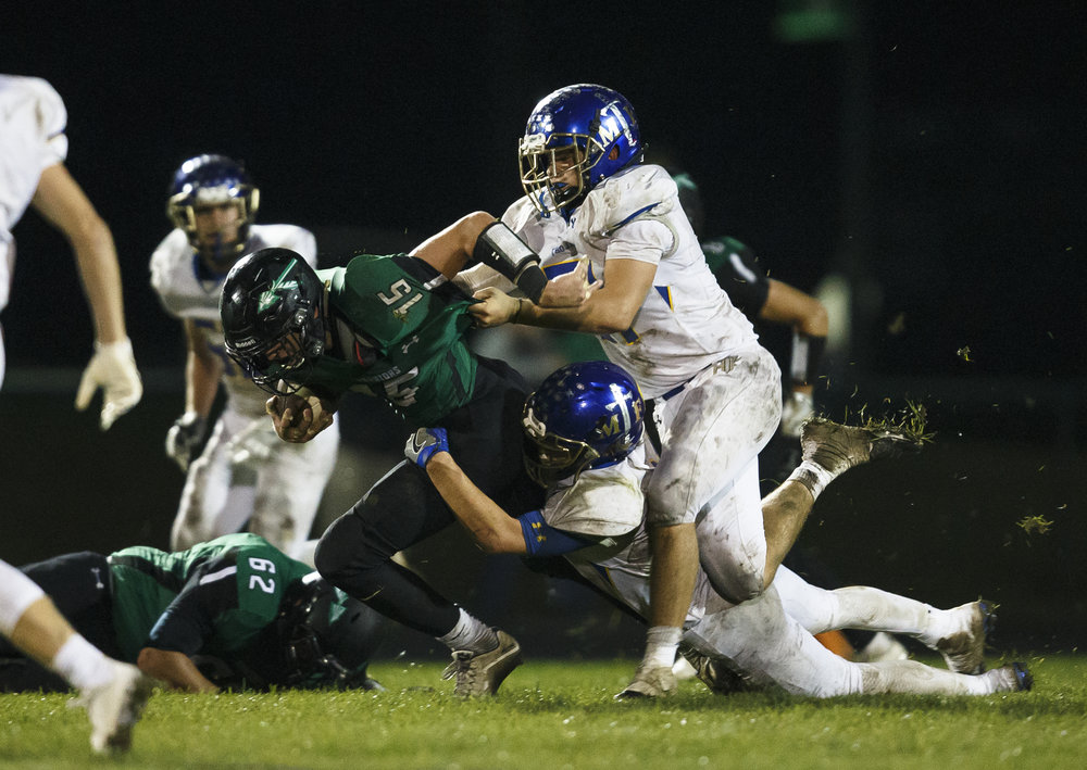 Athens' Hunter Maxwell (15) is brought down by Maroa-Forsyth's Jaxson Nelson (34) and Maroa-Forsyth's Wesley Livingood (51) on a run in the second half at Athens High School, Friday, Sept. 30, 2016, in Athens, Ill. Justin L. Fowler/The State Journal-Register