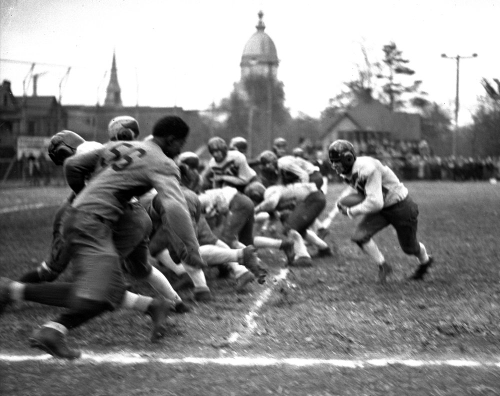 Springfield High School defeated Peoria Central High School 19-6 in action on the Senators' home field on Lewis Street, October 31, 1931. Capitol in background. Illinois State Journal glass plate negative/Sangamon Valley Collection at Lincoln Library. All Rights Reserved, The State Journal-Register. C-98-724, neg# 1297