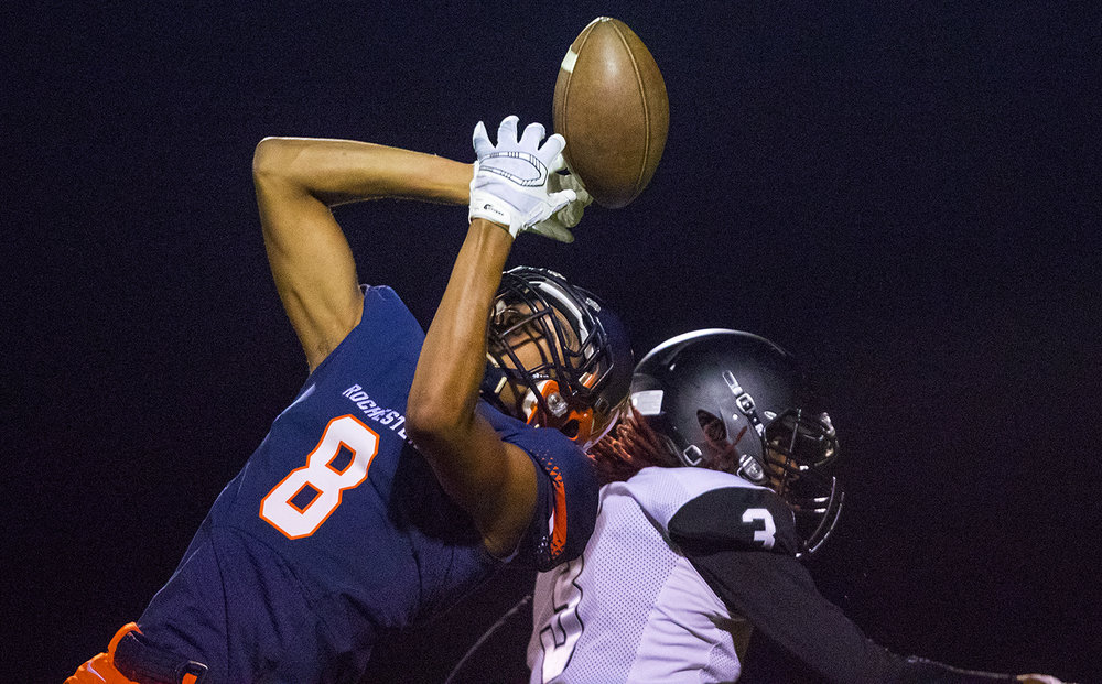 Rochester's Collin Stallworth leaps for an incomplete pass in front of Decatur Eisenhower's Stefon Jarrett at Rochester High School Friday, Oct. 14, 2016. Ted Schurter/The State Journal-Register
