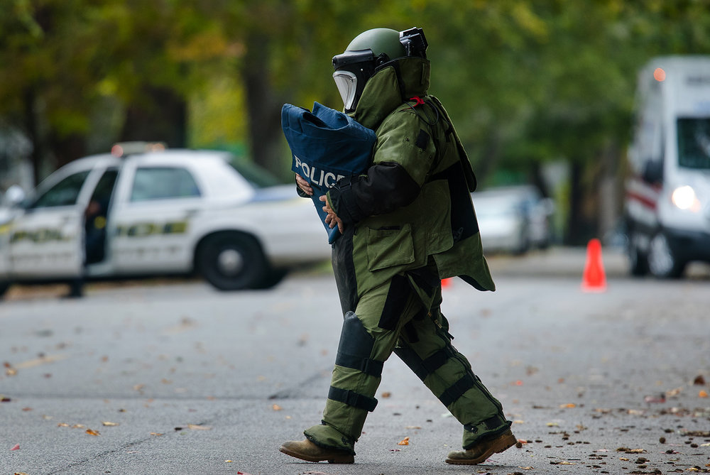 An Illinois Secretary of State Bomb Squad member carries a device found on the front steps of a home on West Edwards Street to a containment vessel Saturday, Oct. 15, 2016. Ted Schurter/The State Journal-Register
