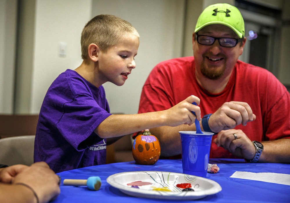 Levi Muller, 7, loads up a sponge brush with paint as he fills the canvas of a small pumpkin along with his father David Muller, and mother Kathie (Not Pictured), during a Pumpkin Painting event for children and their families that have benefited from the money raised for the Children's Miracle Network through the University of Illinois Springfield Dance Marathon Event at the Lincoln Residence Hall on the campus of the University of Illinois Springfield, Monday, Oct. 3, 2016, in Springfield, Ill. Levi has benefited from the money raised through the Dance Marathon with equipment used for the therapy he receives at St. John's Children's Hospital for autism spectrum disorder. Justin L. Fowler/The State Journal-Register