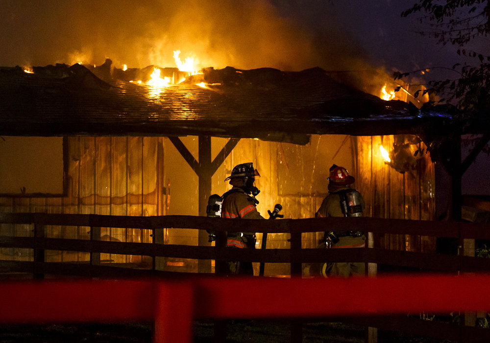 Firefighters from the Springfield Fire Department work the scene of a fully engulfed barn fire south of Memorial Health System's Koke Mill Medical Center, Tuesday, Oct. 4, 2016, in Springfield, Ill. There were two horses in the barn at the time of the fire, firefighters were told, but both were able to get out safely. Justin L. Fowler/The State Journal-Register