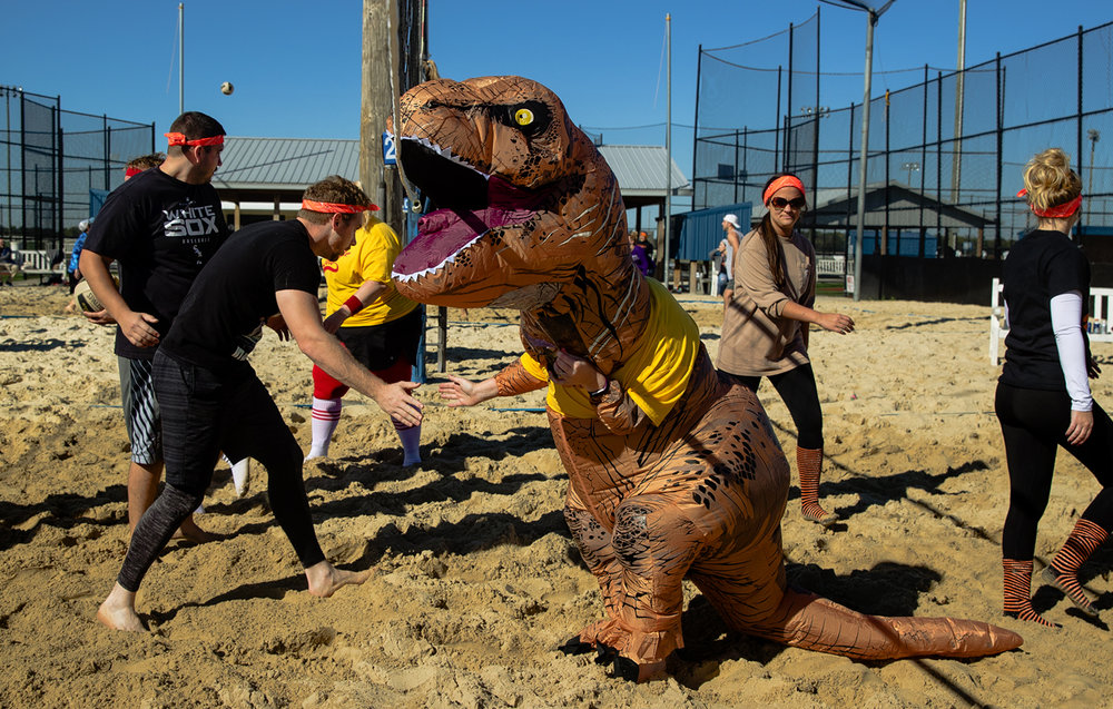 Hannah Heinzel's oversized inflatable dinosaur head catches the net as she shakes hands at the conclusion of a game during the Monster Match Sand Volleyball Tournament at Spartan Sports Park Saturday, Oct. 8, 2016. Proceeds from the event, sponsored by The Center for Youth and Family Solutions, are used to help local foster care children and their families. Ted Schurter/The State Journal-Register