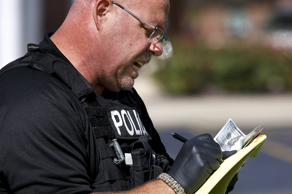 Det. Benny Perkins, a crime scene evidence technician with the Springfield Police Department, records information on money found in the grass near the entrance to Chase Bank at 2801 Greenbriar Rd. Friday, Oct. 7, 2016. A man police believe may have been involved in two other bank robberies in the area, walked into the bank and demanded money. Rich Saal/The State Journal-Register