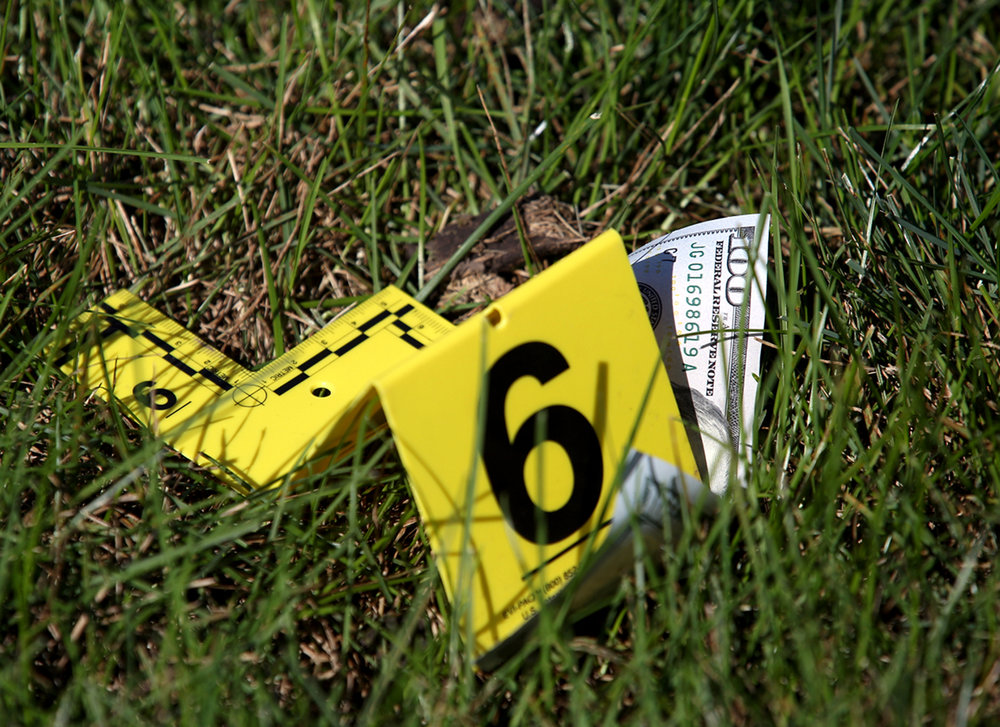 A police evidence marker rests on a $100 bill laying in the grass near the entrance to Chase Bank at 2801 Greenbriar Rd. Friday, Oct. 7, 2016. A man police believe may have been involved in two other bank robberies in the area, walked into the bank and demanded money and apparently dropped some as he left the bank. Rich Saal/The State Journal-Register