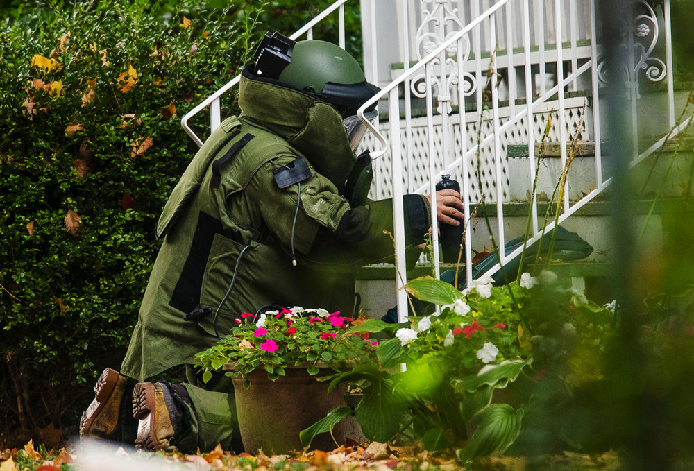 An Illinois Secretary of State Bomb Squad member picks up a device found on the front steps of a home on West Edwards Street before carrying it back to a containment vessel Saturday, Oct. 15, 2016. Ted Schurter/The State Journal-Register