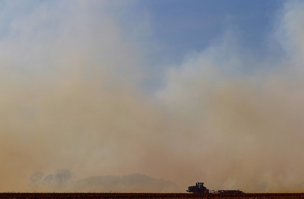 A tractor tills the ground near a wind-driven field fire to create a fire break west of New Berlin Monday, Oct. 17, 2016. Ted Schurter/The State Journal-Register
