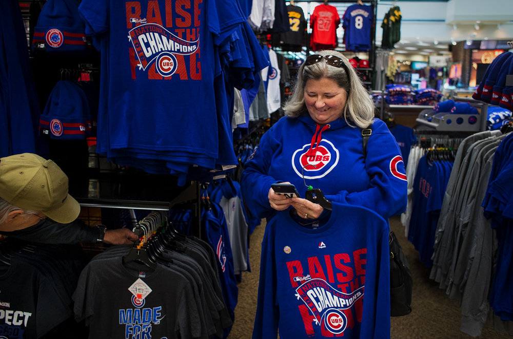Nancy Phillips texts with her friends for whom she was picking up Chicago Cubs merchandise at Scheels Monday, Oct. 24, 2016. Phillips said the adrenaline high from attending the game Saturday when the Cubs won the National League Championship series against the Los Angeles Dodgers to advance to the World Series for the first time since 1945 is just now starting to wear off. Ted Schurter/The State Journal-Register